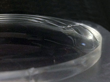 A glass lens displaying its newly aquired hydrophilic coating after plasma treatment
