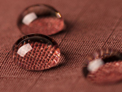 Colored water droplets on a plasma treated textile surface to show hydrophobic coatings